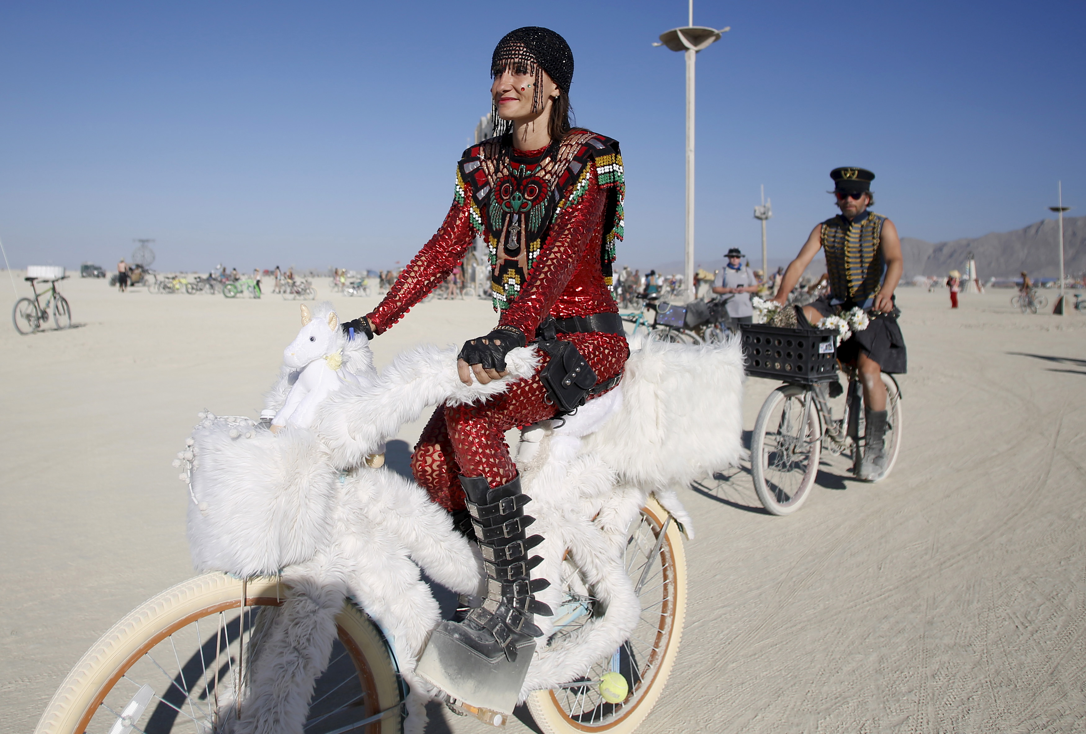 "Bibi rides her bike on the Playa during the Burning Man 2015 ""Carnival of Mirrors"" arts and music festival in the Black Rock Desert of Nevada, August 31, 2015. Approximately 70,000 people from all over the world are gathering at the sold-out festival to spend a week in the remote desert to experience art, music and the unique community that develops. REUTERS/Jim Urquhart FOR USE WITH BURNING MAN RELATED REPORTING ONLY. FOR EDITORIAL USE ONLY. NOT FOR SALE FOR MARKETING OR ADVERTISING CAMPAIGNS. NO THIRD PARTY SALES. NOT FOR USE BY REUTERS THIRD PARTY DISTRIBUTORS - RTX1QINK"